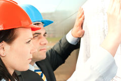 Director with subordinates on construction site. Director and engineers on construction site of shopping center Royalty Free Stock Image