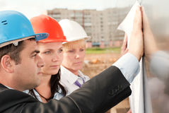 Director with subordinates on construction site. Director and engineers on construction site of shopping center Royalty Free Stock Images