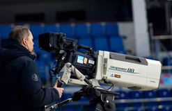 Director and TV camera. MOSCOW - JANUARY 29, 2016: Unidentified director filming hockey game Sweden vs Czech on League of World legends of Ice hockey royalty free stock image