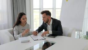 Director y empleado de sexo femenino que trabajan en la tabla en oficina, el jefe sugiere las ideas en la sala de conferencias, h almacen de metraje de vídeo
