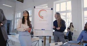 Directores empresariales de sexo femenino jovenes felices que discuten el trabajo con los colegas multiétnicos en el seminario de almacen de video