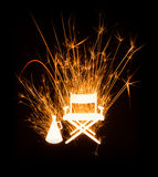 Director's chair and megaphone in glowing sparkler on dark background Stock Photography
