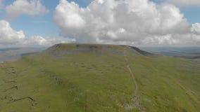 Direita para a esquerda uma metragem sideway aérea de uma montanha rochosa da cimeira com o trajeto verde da inclinação e da fuga video estoque