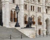 Direito de duas estátuas de bronze do leão que flanqueiam a entrada do leste da construção húngara do parlamento, Budapest foto de stock royalty free