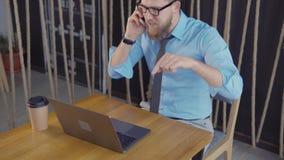 Direktören av företaget talar vid mobiltelefonen i regeringsställning, ser bärbara datorn stock video