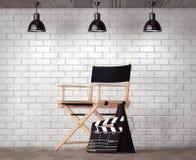 Direktörstol, filmClapper och megafon framme av tegelsten Wa Arkivfoto