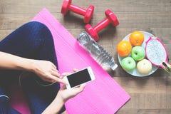 Direkt över av kvinnan i konditionkläder genom att använda mobiltelefonen med sportutrustningar och frukter på golvet, sunt royaltyfri foto