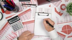 Direkt über der Ansicht des Geschäftsmannes Finanzierung bearbeitend und berechnend, liest und schreibt Berichte Concep Finanzbuc stock footage