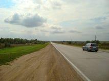 Direkt asfaltväg till och med bygden under himlen, som molnen svävar på royaltyfria foton