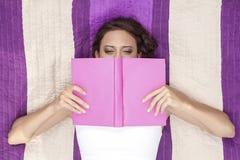 Direkt ovannämnt skott av kvinnabeläggningframsidan med boken, medan ligga på den randiga picknickfilten Arkivbild