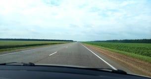 Direkt väg längs gröna fält arkivfoto