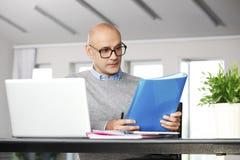 Direktor, der an Geschäftsbericht arbeitet Lizenzfreie Stockfotos