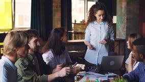Direktor der jungen Frau des Kleinunternehmens spricht mit ihren Angestellten, die bei Tisch Geschäftstreffen im modernen Büro ab stock footage