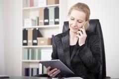 Direktorin, die ein Tablet beim Ersuchen um Telefon hält Lizenzfreie Stockfotografie