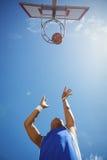 Diretamente abaixo do tiro do adolescente masculino que joga o basquetebol foto de stock