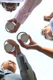 Diretamente abaixo do tiro dos empresários que mantêm copos descartáveis contra o céu claro imagem de stock