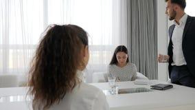 Diretor agressivo e empregados do sexo feminino na tabela no escritório, água de vidro disponivel da posse má do chefe na sala de video estoque