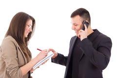 Diretor de sorriso no telefone e em seu secretário que escrevem para baixo não Fotos de Stock Royalty Free