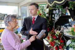 Diretor fúnebre que mostra a mulher a chapa memorável fotografia de stock royalty free