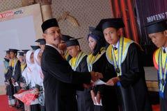 Diretor que dá o certificado à cerimônia de graduação do estudante foto de stock
