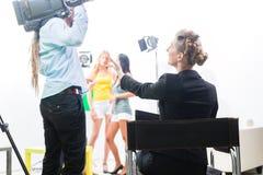 Diretor que dá o sentido do operador cinematográfico para a produção video Fotografia de Stock Royalty Free