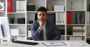 Diretor que senta-se na tabela no escritório branco e que põe a mão à testa