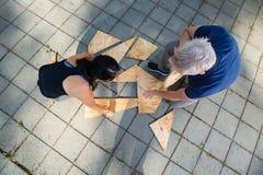 Direttamente sopra il colpo degli amici che risolvono puzzle di legno delle plance Fotografia Stock Libera da Diritti
