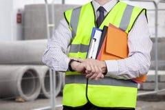 Direttore dei lavori nell'alta visibilità che controlla il tempo sul sito Immagine Stock