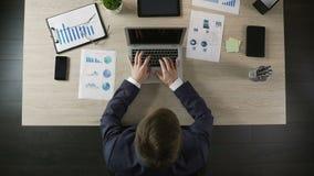 Direttore di società maschio che scrive sul computer portatile, sul programma di pianificazione o sulla strategia aziendale video d archivio