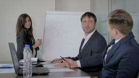 Direttore generale Presents della donna un piano di progetto ai colleghi ad una riunione nell'ufficio archivi video