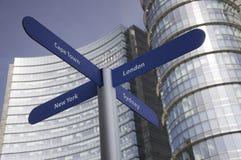 Direzione dei posti differenti nel mondo con i grattacieli come fondo Fotografia Stock