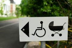 Direzione del segno del passeggiatore e della sedia a rotelle di bambino fotografia stock