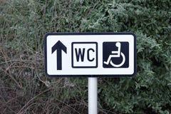 Direzione disabile della freccia del segnale stradale della toilette del WC del pubblico fotografie stock libere da diritti