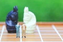 Direzione per il gioco di successo, condizione miniatura dell'uomo d'affari sul fondo di scacchi e della scacchiera, sull'investi fotografia stock