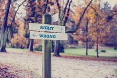 Direzioni opposte verso giusto e sbagliato Immagine Stock