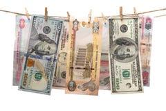 Dirham en dolar bankbiljetten die op een kabel met wasknijper hangen stock foto
