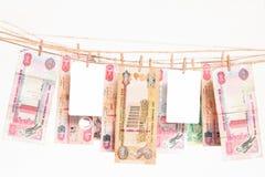 Dirhambankbiljetten die op een kabel met aan lege betaalpassen tussen hen hangen stock afbeeldingen