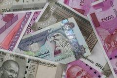 Dirhames de los UAE entre los nuevos billetes de banco indios de la moneda de las rupias imagen de archivo