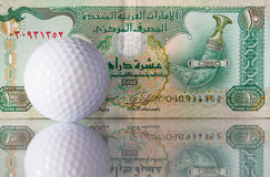 Dirhams and golf ball Royalty Free Stock Images