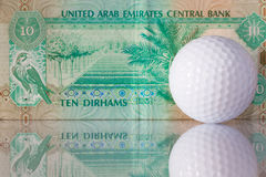 Dirhams and golf ball Stock Photos