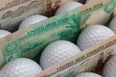 Dirhams and golf balls Royalty Free Stock Photo