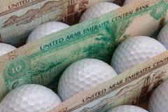 Dirhams and golf balls Royalty Free Stock Photo