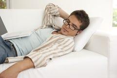 Diriga l'uomo di tecnologia che dorme sul sofà Fotografia Stock