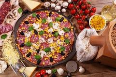 Diriga la pizza fatta con gli ingredienti sulla vista da tavolo Immagine Stock Libera da Diritti