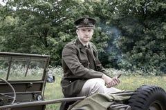 Dirigeant d'armée beau de GI de l'Américain WWII en cigare de tabagisme uniforme tout en se reposant sur Willy Jeep photo stock