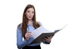 Dirigeant féminin passant en revue dans un dossier Photographie stock libre de droits