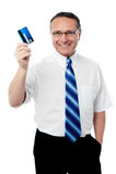 Dirigente anziano che mostra la sua carta di credito Fotografia Stock