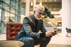 Dirigente anziano che utilizza telefono nell'ingresso dell'ufficio fotografie stock libere da diritti
