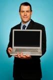 Dirigente aziendale che mostra computer portatile voi Fotografia Stock