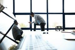 Dirigente aziendale nella regolazione architettonica moderna che guarda con confidenza dalle alte finestre di aumento Fotografia Stock Libera da Diritti